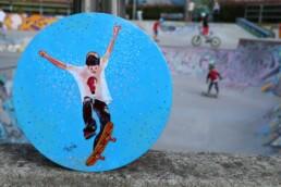 Skater painting on vinyl record at skate park, by Claudio Bindella