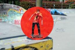Skater painting on vinyl record at skate park By Claudio Bindella